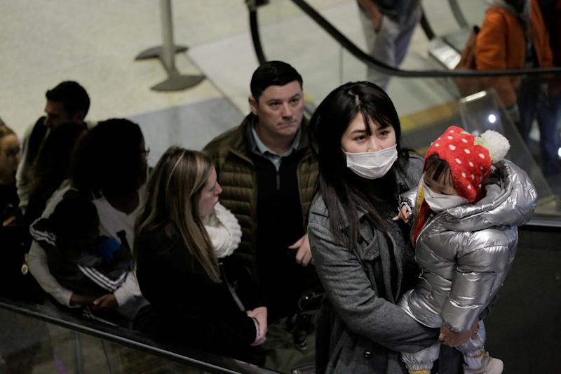 Travellers wearing masks arrive on a direct flight from China at Seattle-Tacoma International Airport