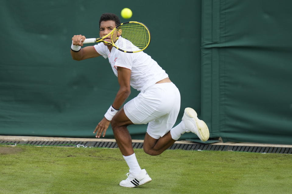 Canada's Felix Auger-Aliassime plays a return to Brazil's Thiago Monteiro during the men's singles first round match against on day three of the Wimbledon Tennis Championships in London, Wednesday June 30, 2021. (AP Photo/Kirsty Wigglesworth)