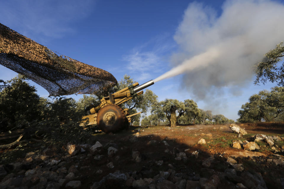 Turkish backed rebel fighters fire a howitzer toward Syrian government's forces positions near the village of Neirab in Idlib province, Syria, Thursday, Feb. 20, 2020. Two Turkish soldiers were killed Thursday by an airstrike in northwestern Syria, according to Turkey's Defense Ministry, following a large-scale attack by Ankara-backed opposition forces that targeted Syrian government troops. (AP Photo/Ghaith Alsayed)