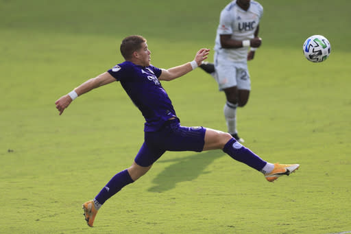 Orlando City forward Chris Mueller (9) jumps to control the ball against the New England Revolution during the first half of an MLS playoff soccer match, Sunday, Nov. 29, 2020, in Orlando, Fla. (AP Photo/Matt Stamey)
