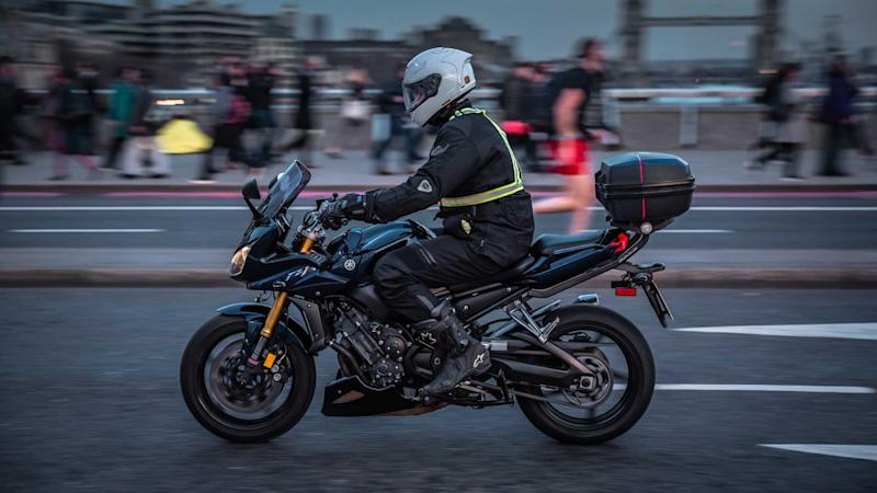 Motorcyclist and commuters crossing London Bridge during rush hour