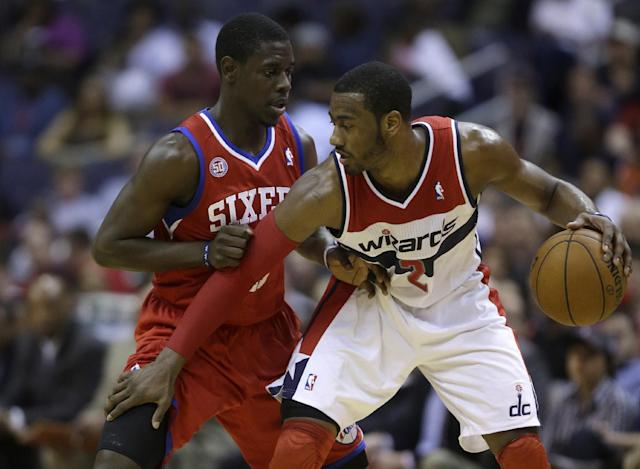 "FILE - In this April 12, 2013 file photo, Washington Wizards point guard John Wall, right, is guarded by Philadelphia 76ers point guard Jrue Holiday during the second half of an NBA basketball game in Washington. The aim is pretty clear for Wall and the rest of the Washington Wizards: get to the postseason. Team president Ernie Grunfeld says so. As does coach Randy Wittman. Speaking at a joint news conference Wednesday, Grunfeld says, ""Our initial goal is to be a playoff contender and, ultimately, by the end of the year, make the playoffs."" Wittman adds, ""We want to make the playoffs. ... And there's no reason why we can't."" Washington went 29-53 last season, missing out on the postseason for the fifth consecutive year. (AP Photo/Evan Vucci, File)"