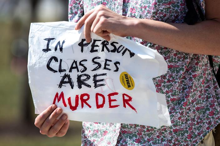 """A persons hold a sign reading, """"In person classes are murder"""" during a protest Aug. 10 on the University of Iowa campus in Iowa City, Iowa."""