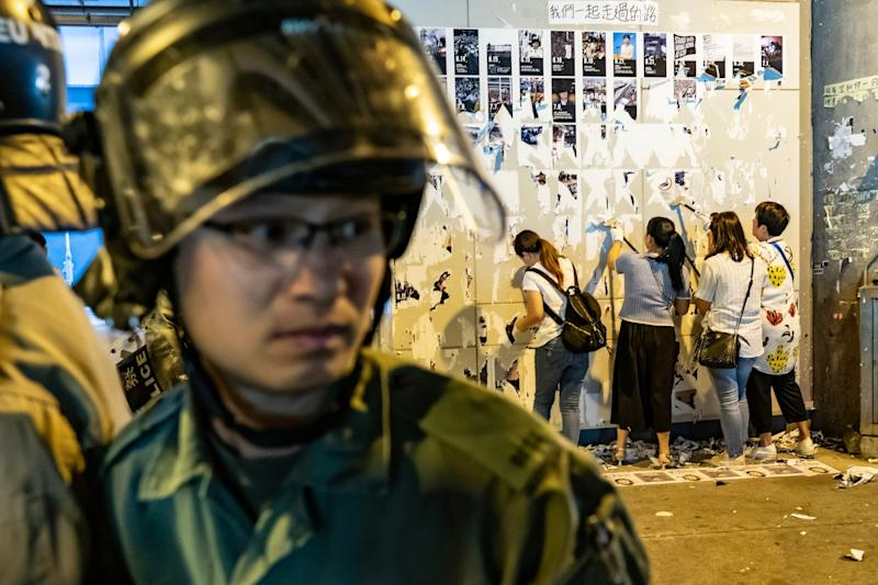 Pro-China supporters tear down so-called 'Lennon walls' of protest messages as riot police stand guard (Getty Images)