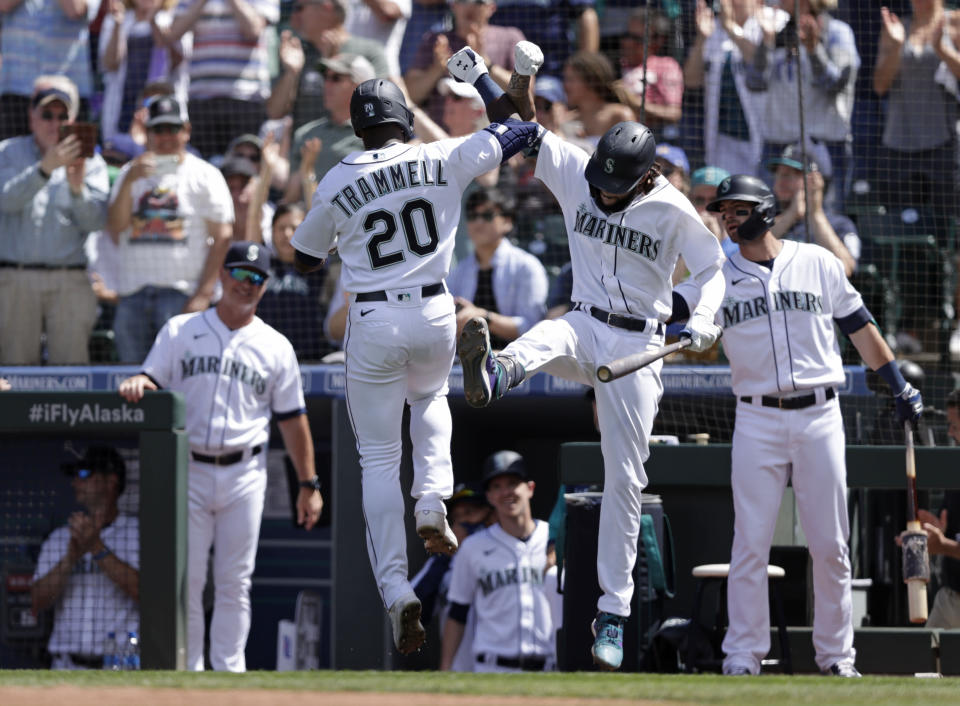 Seattle Mariners' Taylor Trammell is greeted at home by J.P. Crawford after hitting a solo home run on a pitch from Colorado Rockies starting pitcher German Marquez during the sixth inning a baseball game, Wednesday, June 23, 2021, in Seattle. (AP Photo/John Froschauer)