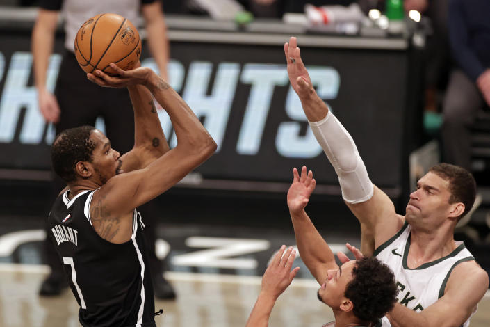 Brooklyn Nets forward Kevin Durant (7) shoots over Milwaukee Bucks center Brook Lopez during the first half of an NBA basketball game Monday, Jan. 18, 2021, in New York. (AP Photo/Adam Hunger)
