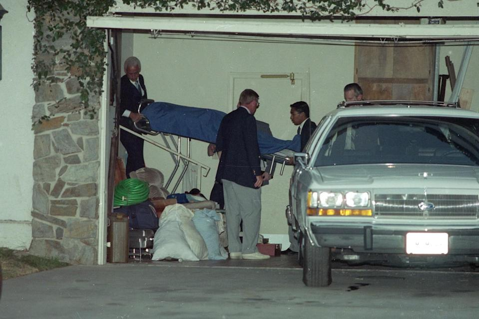 Orange County Coroner's personnel remove the body of Donnie Moore from his home.