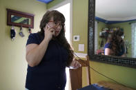 Allison Cullen, of Brockton, Mass.,speaks on the phone, Thursday, July, 22, 2021, with her husband Flavio Andrade Prado, a Brazilian national, from her home in Brockton. Prado is being held by Immigration and Customs Enforcement, or ICE, at the Plymouth County House of Corrections. Cullen, a mother of two, says she and her children haven't been able to visit her husband since before the pandemic. The number of detainees nationwide has more than doubled since the end of February, to nearly 27,000, according to recent data from U.S. Immigration and Customs Enforcement. (AP Photo/Steven Senne)