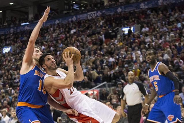 Toronto Raptors' Venezuelan guard Grevis Vasquez, second from left, shoots against New York Knicks' guard Beno Udrih, left, of Slovenia, as Knicks' Tim Hardaway Jr. watches during first-half NBA basketball game action in Toronto, Saturday, Dec. 28, 2013. (AP Photo/The Canadian Press, Chris Young)