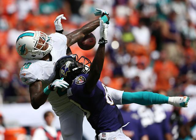 Miami Dolphins cornerback Nolan Carroll (28), left, prevents a reception by Baltimore Ravens wide receiver Deonte Thompson (83) during the first half of an NFL football game, Sunday, Oct. 6, 2013, in Miami Gardens, Fla. (AP Photo/J Pat Carter)
