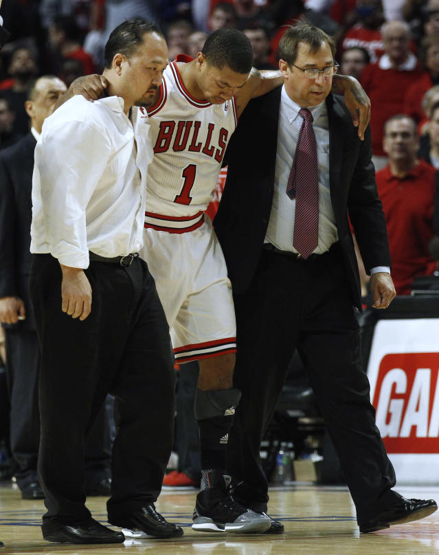 Chicago Bulls' Derrick Rose (C) is helped off the court after getting hurt during the second half of their NBA Eastern Conference quarter-final playoff basketball game against the Philadelphia 76ers in Chicago April 28, 2012. REUTERS/Jim Young (UNITED STATES - Tags: SPORT BASKETBALL)