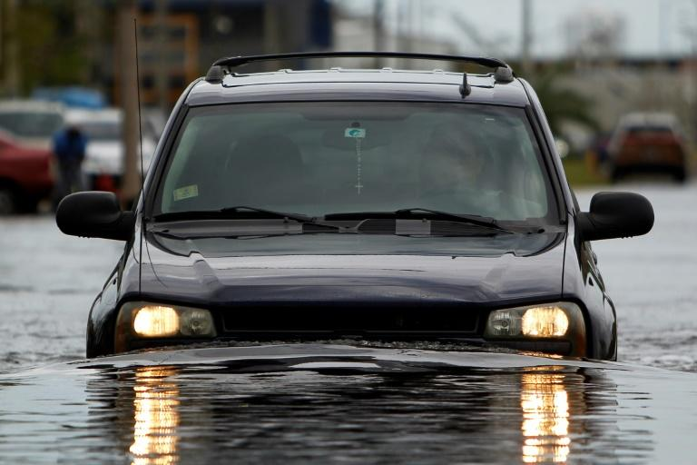 A car drives though a flooded street in the aftermath of Hurricane Maria in San Juan, Puerto Rico