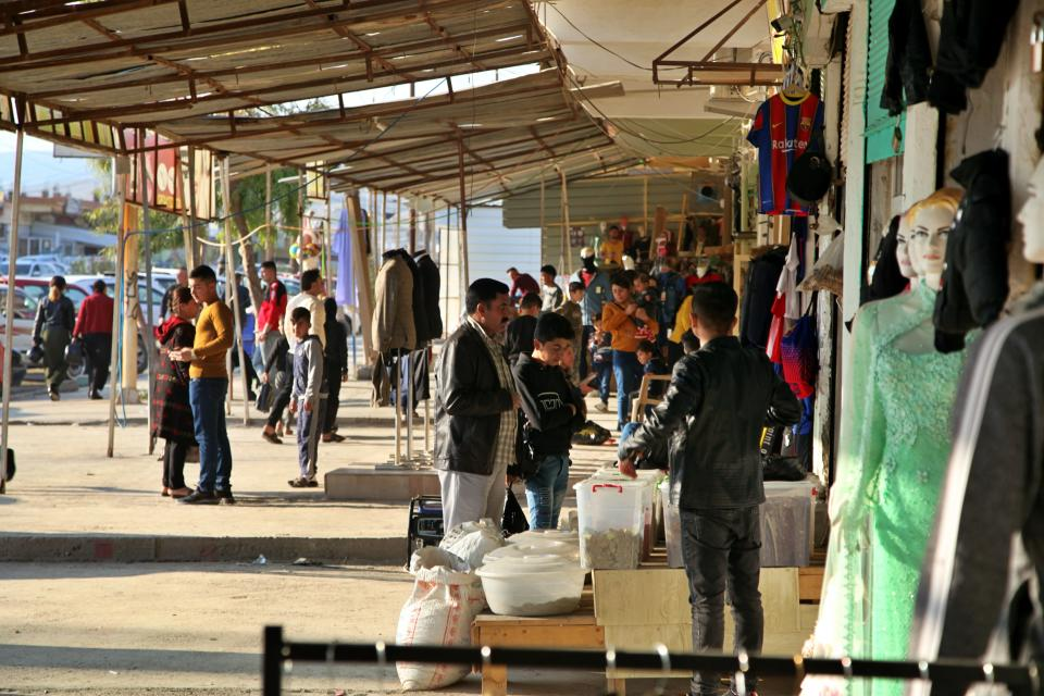 Crowds gather in the city center after a federal government order restored the central government's authority in Sinjar, Iraq. Friday Dec. 24, 2020. A new agreement aims to bring order to Iraq's northern region of Sinjar, home to the Yazidi religious minority brutalized by the Islamic State group. Since IS's fall, a tangled web of militia forces have run the area, near the Syrian border. Now their flags are coming down, and the Iraqi military has deployed in Sinjar for the first time in nearly 20 years. (AP Photo/Samya Kullab)