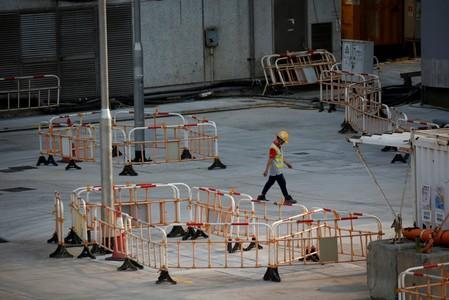 FILE PHOTO: Worker walks at a construction site of MTR station at Hung Hom in Hong Kong