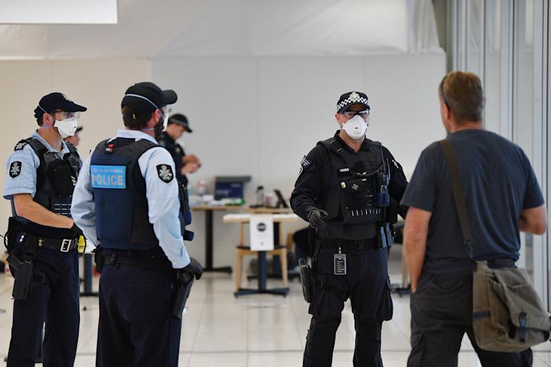 Police wearing face masks are seen at Adelaide Airport. A new plan may see people who breach self-isolation or quarantine forced to wear tracking devices.