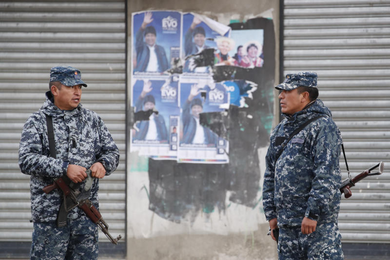 Soldiers stand in front of electoral posters of former President Evo Morales in El Alto, outskirts of La Paz, Bolivia, Tuesday, Nov. 12, 2019. Bolivia faced political vacuum Tuesday, while Morales fled the country on a Mexican plane following weeks of widespread protests fed by allegations of electoral fraud in the Oct. 20 presidential election that he claimed to have won (AP Photo/Natacha Pisarenko)
