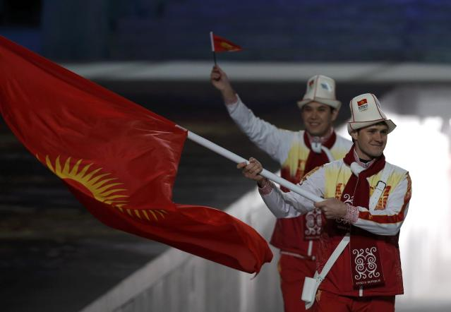 Kyrgyzstan's flag-bearer Dmitry Trelevski leads his country's contingent during the athletes' parade at the opening ceremony of the 2014 Sochi Winter Olympics, February 7, 2014. REUTERS/Phil Noble (RUSSIA - Tags: OLYMPICS SPORT)