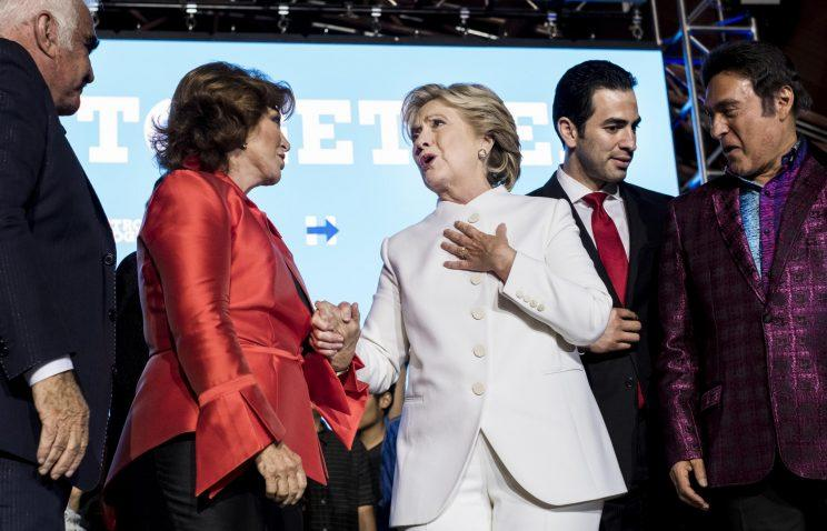 Hillary Clinton and singer Vicente Fernandez, left, stand on stage together at debate watch party in North Las Vegas, Nev. (Photo: Andrew Harnik/AP)