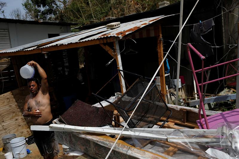 A manshowers with water from a well on a Canovanas street on Sept. 26.