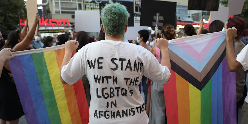 """A person holds a rainbow flag and wears a shirt that says, """"We stand with the LGBTQs in Afghanistan."""""""