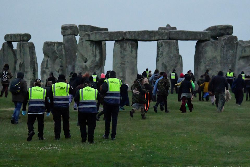 Security looks on as people run to Stonehenge (REUTERS)