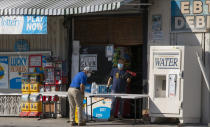 "FILE - In this April 1, 2020, file photo, a customer wears a face mask as he purchases drinking water at a ""Grab-and-Go"" market table in the Boyle Heights area of Los Angeles. State governments will get a big influx of federal money from the $1.9 trillion COVID-19 relief package that could suddenly enable them to undertake large, expensive projects that have long been on their to-do lists, including high-speed internet for rural areas and drinking water improvements. (AP Photo/Damian Dovarganes, File)"
