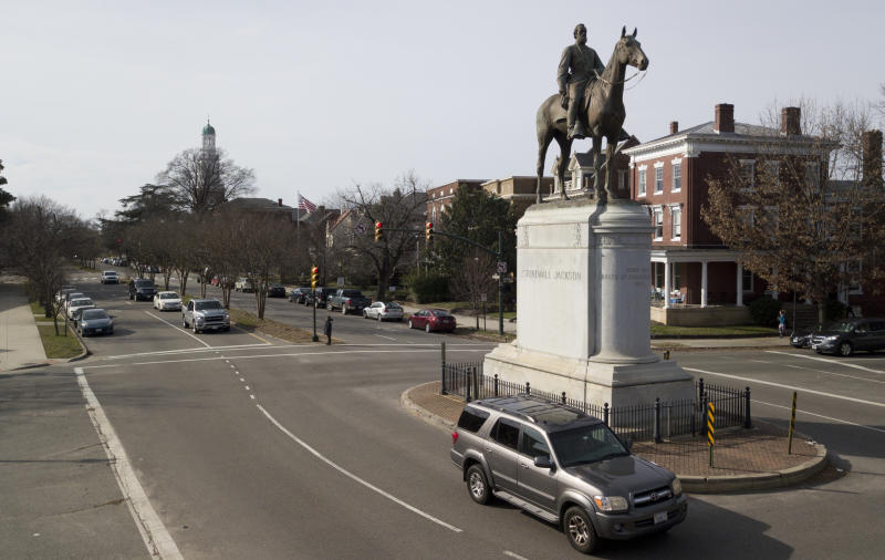In this Jan. 27, 2019, photo traffic passes by the statue of Confederate General Stonewall Jackson at the intersection Traffic passes by the statue of Confederate General Stonewall Jackson at the intersection of Monument Avenue and The Boulevard in Richmond, Va., Sunday, Jan. 27, 2019. A city councilwoman and others are attempting to get the Boulevard named after tennis star Arthur Ashe. (AP Photo/Steve Helber)