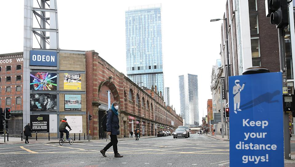 A person wearing face masks walks across Deansgate in Manchester as the city is waiting to find out if the region will be placed into the Very High category with tier 3 lockdown restrictions to curb the spread of coronavirus. (Photo by Martin Rickett/PA Images via Getty Images)