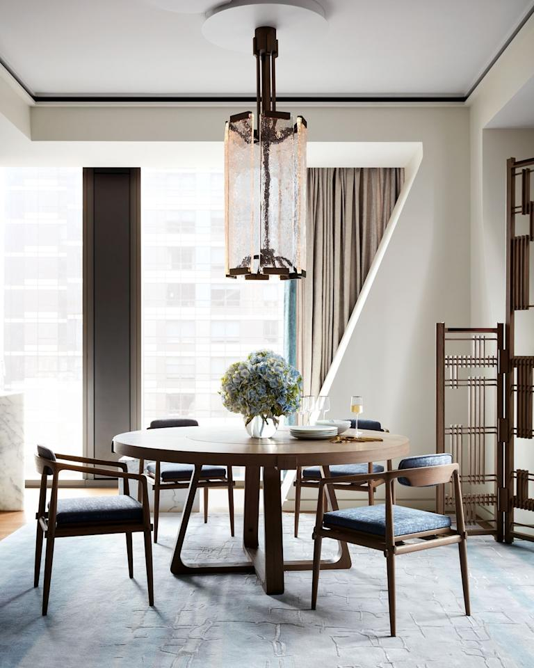 <p>Just off the kitchen is a sleek midcentury-modern table and chairs, with a handmade screen partition designed by Fu and a sculptural glass pendant.</p>