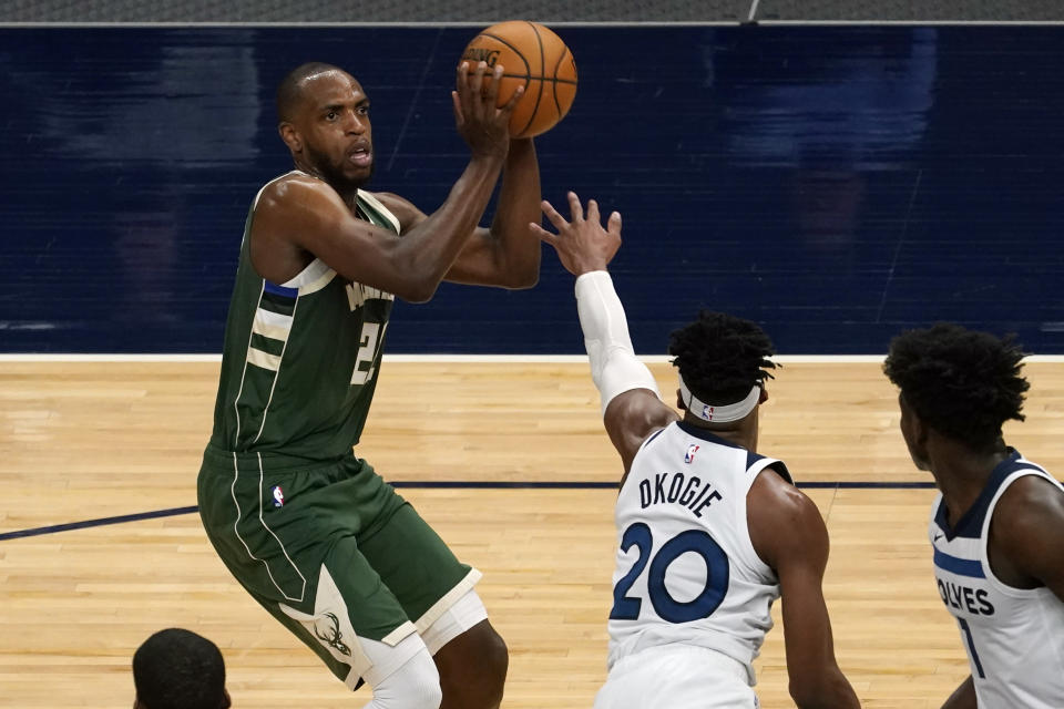 Milwaukee Bucks' Khris Middleton, left, eyes the basket as Minnesota Timberwolves' Josh Okogie rushes in during the second half of an NBA basketball game Wednesday, April 14, 2021, in Minneapolis. Middleton led his team's scoring as the Bucks won 130-105. (AP Photo/Jim Mone)