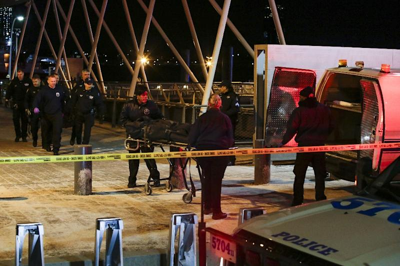 Police officers remove bodies from the scene of a helicopter crash in Manhattan's East River that left five people dead (AFP Photo/EDUARDO MUNOZ ALVAREZ)