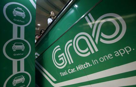 FILE PHOTO -  Commuters pass Grab transport booking service app advertisements at a train station in Singapore