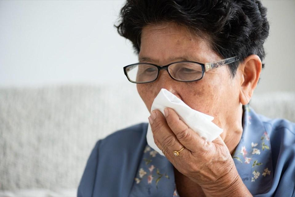 older woman coughing into tissue