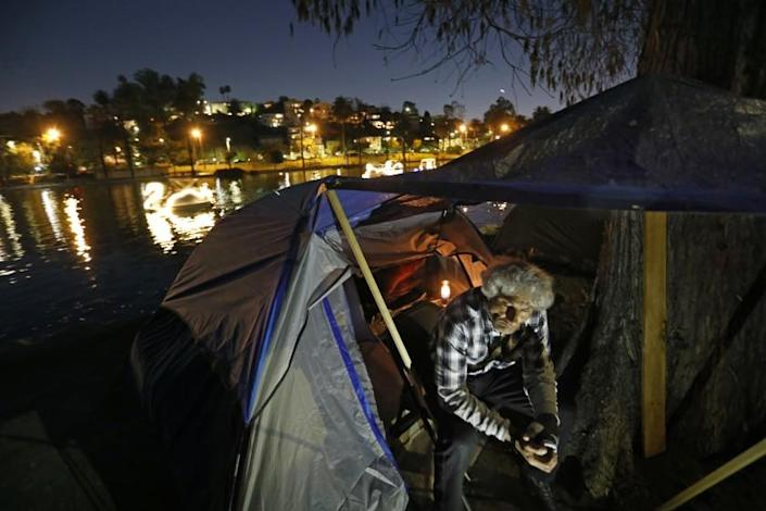 LOS ANGELES, CA - MARCH 04, 2021: Gene Ostrin, age 53, has been living in a tent on the edge of Echo Park while he mourns the loss of his partner who recently passes away. He is originally from Chicago. Echo Park has become a location where homeless people have taken up residence. Photograph taken on March 4, 2021. (Carolyn Cole / Los Angeles Times)