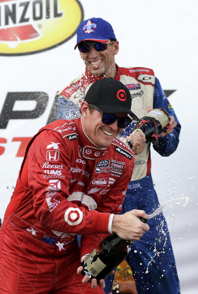 Winner Scott Dixon, front, of New Zealand, is sprayed by third place finisher Justin Wilson, of Great Britain, after the first IndyCar Grand Prix of Houston auto race, Saturday, Oct. 5, 2013, in Houston. (AP Photo/David J. Phillip)