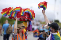 A woman offers LGBT pride flags to football supporters outside of the stadium before the Euro 2020 soccer championship group F match between Germany and Hungary at the Allianz Arena in Munich, Germany, Wednesday, June 23, 2021. (AP Photo/Matthias Schrader)
