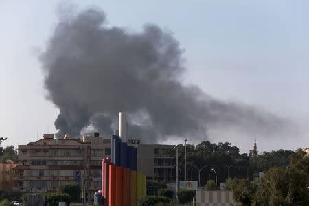 Black smoke billows in the sky above areas where clashes are taking place between pro-government forces and the Shura Council of Libyan Revolutionaries in Benghazi