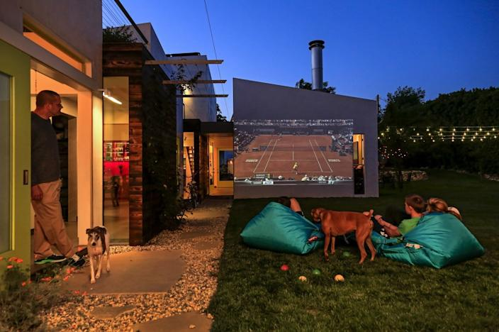"Activity spills freely between inside and out. Movies (or, here, a tennis match) are often projected onto an outside wall. <span class=""copyright"">(Ricardo DeAratanha / Los Angeles Times)</span>"