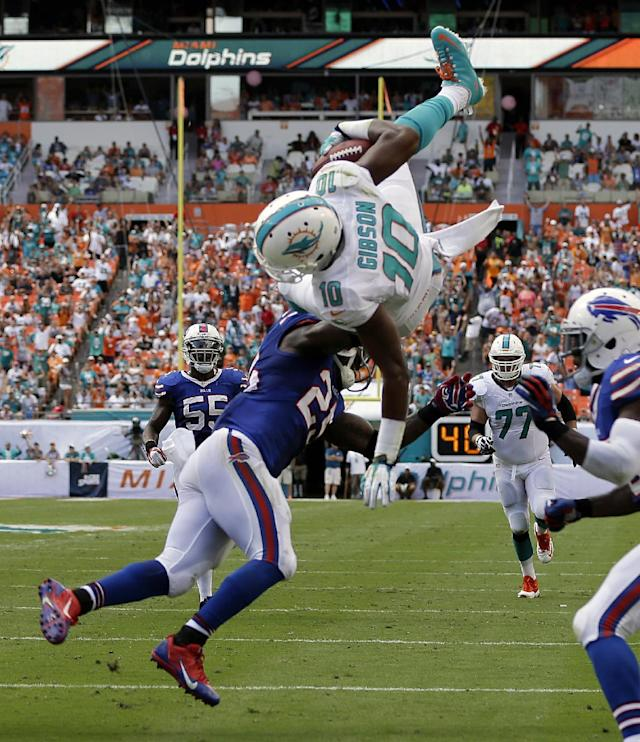 Miami Dolphins wide receiver Brandon Gibson (10) jumps over Buffalo Bills free safety Aaron Williams (23) and strong safety Da'Norris Searcy (25), obscured at right, for a touchdown during the first half of an NFL football game, Sunday, Oct. 20, 2013, in Miami Gardens, Fla. (AP Photo/Lynne Sladky)