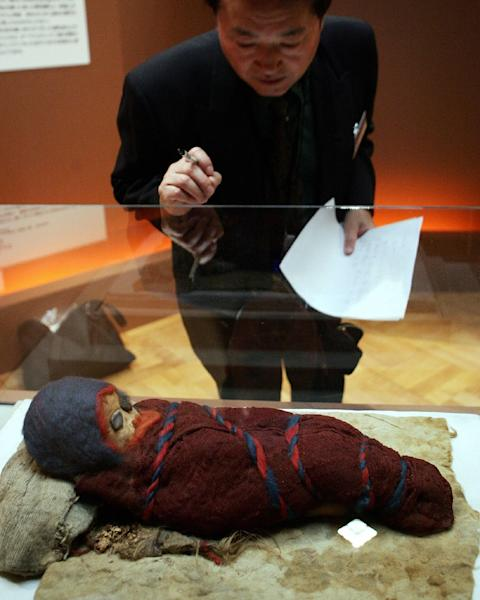 "A journalist looks at a baby mummy which was unearthed at an ancient tomb in Chinese city of Qarqan. The Kyrgyzstan mummy ""has tremendous value in filling in the gap"" as a case study between Xinjiang's Tarim Basin and Western Eurasia, experts say (AFP Photo/TORU YAMANAKA)"