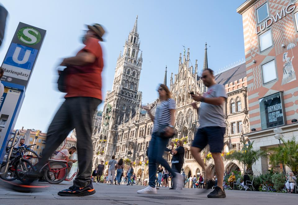 21 September 2020, Bavaria, Munich: Passers-by walk across the Marienplatz in the heart of the Bavarian capital past the town hall. In order to contain the corona virus, the city of Munich wants to make masks mandatory in certain public places and streets in the city centre - if the number of new infections remains at a high level. Photo: Peter Kneffel/dpa (Photo by Peter Kneffel/picture alliance via Getty Images)