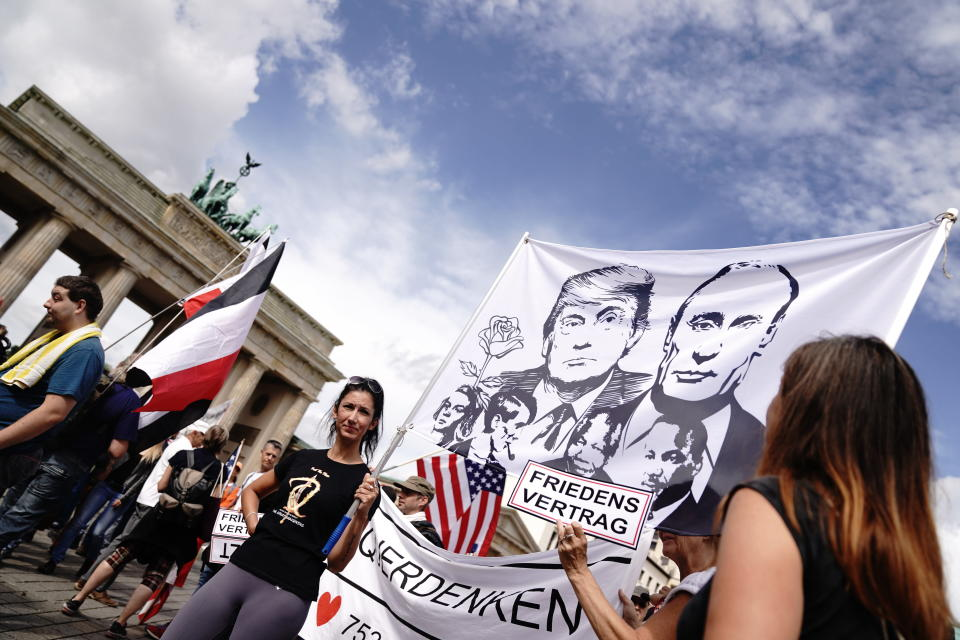 Participants gather at the Brandenburg Gate for a demonstration against the Corona measures and hold a banner with the picture of US President Trump and Russian President Putin in Berlin, Germany, Saturday, Aug. 29, 2020. (Kay Nietfeld/dpa via AP)