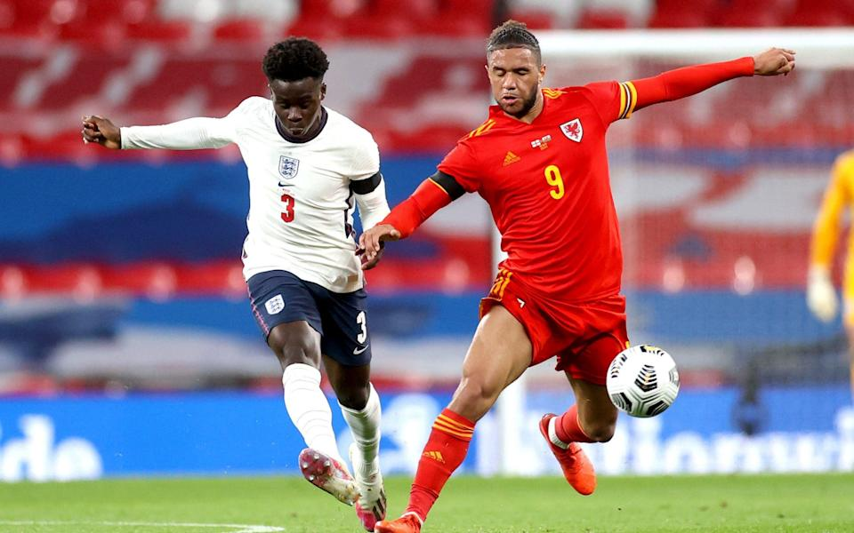 England's Bukayo Saka (left) and Wales' Tyler Roberts battle for the ball during the international friendly match at Wembley Stadium, - PA