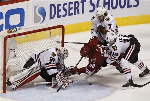 Chicago Blackhawks' Corey Crawford, left, makes a save on a shot by Phoenix Coyotes' Antoine Vermette (50) as Blackhawks' Marcus Kruger (16), of Sweden, and Brent Seabrook (7) defend during the first period in Game 5 of an NHL hockey Stanley Cup first-round playoff series Saturday, April 21, 2012, in Glendale, Ariz.AP Photo/Ross D. Franklin)