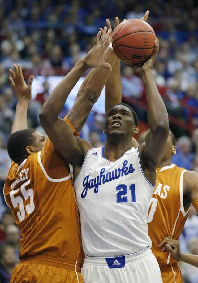 Kansas center Joel Embiid (21) shoots while covered by Texas center Cameron Ridley (55) and forward Jonathan Holmes, back, during the first half of an NCAA college basketball game in Lawrence, Kan., Saturday, Feb. 22, 2014. Embiid was fouled by Holmes on the play. (AP Photo/Orlin Wagner)