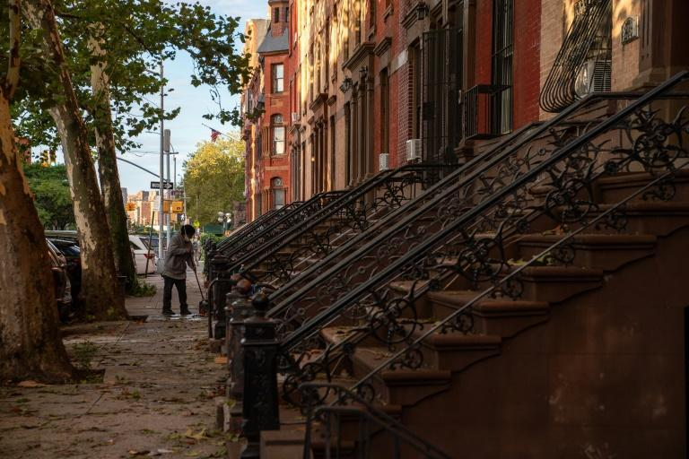 A person sweeps up debris in the front of a brownstone after the extremely heavy rainfall from Hurricane Ida on September 2, 2021, in the Bronx borough of New York City (AFP/David Dee Delgado)