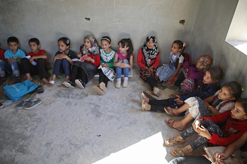 "Displaced children sit on the floor at the ""Buds of Hope"" school in Syria's Aleppo province which has no desks, library or even working toilets (AFP Photo/Aaref WATAD)"