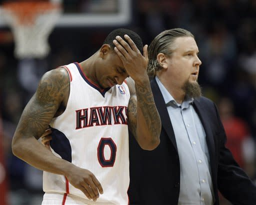 Atlanta Hawks point guard Jeff Teague (0) is helped off the court by trainer Wally Blase after falling and hitting his head during the second quarter of an NBA basketball game against the Indiana Pacers on Wednesday, Feb. 8, 2012, in Atlanta. Teague remained in the game. (AP Photo/John Bazemore)