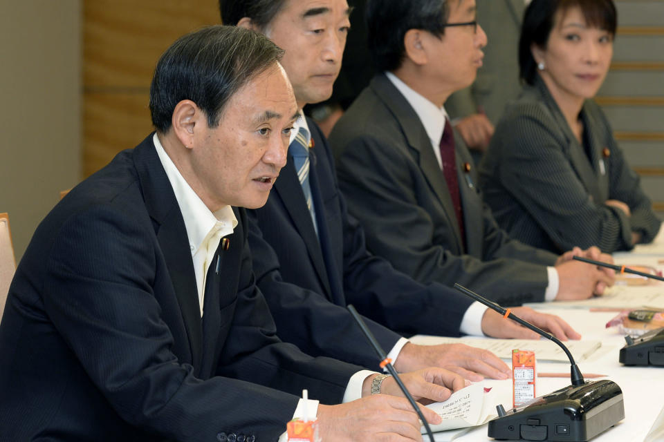 Then Chief Cabinet Secretary Yoshihide Suga, left, speaks at a meeting on food, agriculture and rural areas, at the prime minister's office in Tokyo Oct. 29, 2013. Japan's Parliament elected Suga as prime minister Wednesday, Sept. 16, 2020, replacing long-serving leader Shinzo Abe with his right-hand man. Suga has stressed his background as a farmer's son and a self-made politician in promising to serve the interests of ordinary people and rural communities. (Kyodo News via AP)