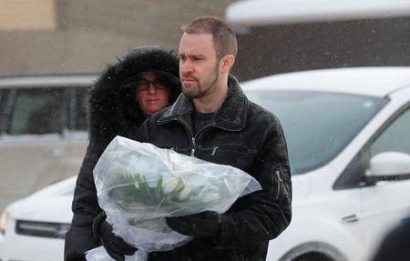 People bring flowers at the scene of a fatal shooting at the Quebec Islamic Cultural Centre in Quebec City. REUTERS/Mathieu Belanger